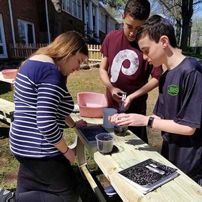 Students working with FOSS materials at an outdoor table
