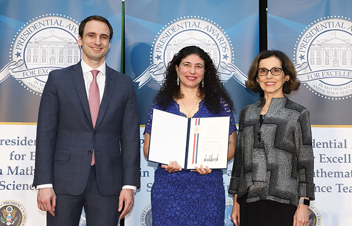Awardee Delara Sharma holding Presidential certificate between Deputy Assistant to the President and Deputy U.S. Chief Technology Officer, Michael Kratsios, and National Science Foundation Director, Dr. France A. Córdova.