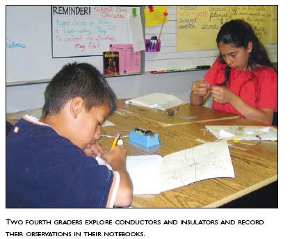 Two fourth-graders explore conductors and insulators and record their observations in their notebooks.
