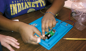 Students working to make a circuit using the FOSS Magnetism and Electricity Module.