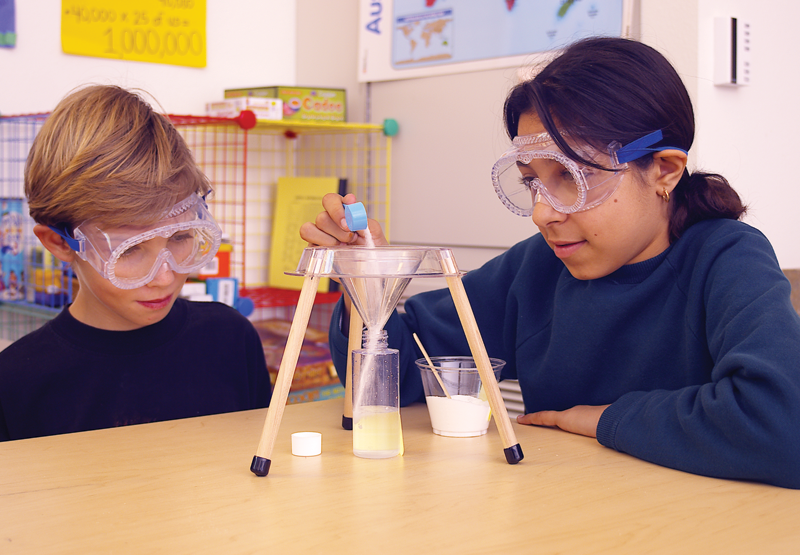 Two students observe a tripod funnel